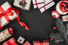 Obere Draufsicht eines roten Bandes, der Weihnachtsgeschenke, der Baumspielwaren und der immergrünen Niederlassung auf einem schw Lizenzfreie Stockbilder