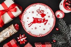 Obere Draufsicht eines roten Bandes, Weihnachtsgeschenke, Baumspielwaren, Rotwildplatte und Immergrün verzweigen sich auf einen s Lizenzfreies Stockbild