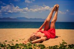 oberes Ansichtmädchen in den Rotlügen auf Sand hebt nackte Beine durch Kriechpflanzen an Stockfotografie