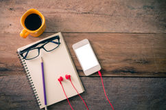 Oberfläche eines Holztischs mit Notizbuch, Smartphone, Gläser stockfotos