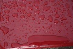 Oberflächenspannung - waterdrops auf einer roten Beschichtung lizenzfreies stockfoto