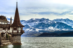 Oberhofen castle tower on alpine background, mountains with snow Royalty Free Stock Photos