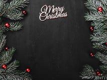 Oberleder, Spitze, Ansicht von oben, immergrüne Niederlassungen, Baumkugeln und weiße Aufschrift der frohen Weihnachten auf schwa lizenzfreies stockbild