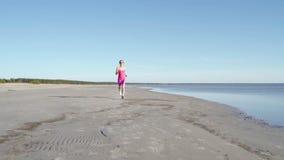 Oberoende idrottsman nen f?r ung kvinna som k?r p? stranden som ?var den kvinnliga l?paren som sprintar utbildning i solig sj?sid lager videofilmer