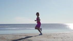 Oberoende idrottsman nen f?r ung kvinna som k?r p? stranden som ?var den kvinnliga l?paren som sprintar utbildning i solig sj?sid stock video