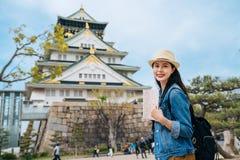 Oberoende lopp i Japan livsstilbegrepp resehandbok för kvinnahandelsresandeinnehav som besöker den osaka slotten bara som bär ryg royaltyfria foton