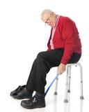 Oberoende pensionär som använder den Assistive dressingapparaten Royaltyfri Foto