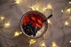Oberseiteansicht einer Schüssel mit Jogurt, Erdbeeren und Blaubeeren über grauen Blättern mit Lichtern stockbilder