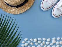 Oberteile, Turnschuhe, ein tropisches Blatt und ein Sommerhut stockfotos