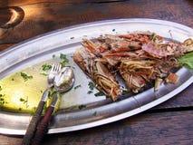 Oberteile von gegessenen großen Garnelen, gebraten im Olivenöl mit Knoblauch und Petersilie auf einem Metallteller Holztisch in e Stockfotografie