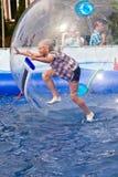 A menina tem o divertimento em uma bola zorbing enorme Foto de Stock