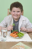 An Obese Boy Eating Vegetables Stock Photography