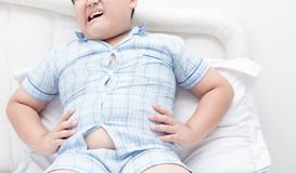 Obese boy overweight stomachache on bed Royalty Free Stock Images