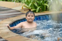 Obese boy relaxing enjoying hot tub bubble bath. Outdoors on summer vacation travel holiday, relaxation concept royalty free stock photos
