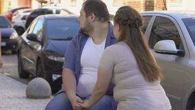 Obese boyfriend looking at slim lady, overweight girlfriend jealous and offended. Stock footage stock footage