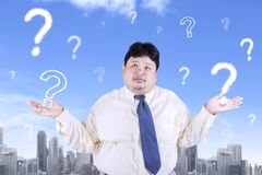 Obese businessman with question marks Stock Image