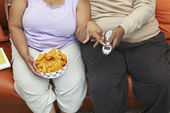 Obese Couple Sitting On Couch. Midsection of an obese couple sitting on couch with nachos and remote control Royalty Free Stock Photography