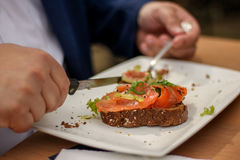 Obese at dinner table eating salmon. Obese male eating salmon bread restaurant Royalty Free Stock Image