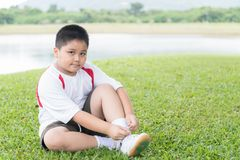 Obese fat asian boy lacing sport shoe. royalty free stock image