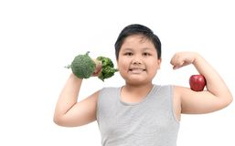 Obese fat boy holding a broccoli dumbbell. And show muscle with apple isolated on white background, diet and exercise for good health concept Stock Photo