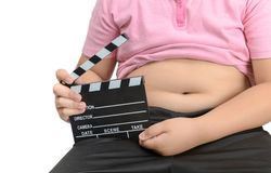Obese fat boy holding clapper board or slate film royalty free stock image