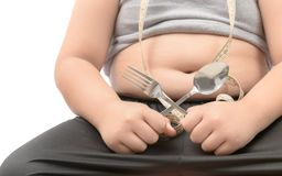 Obese fat boy holding fork and spoon isolated. Over white, diet to lose weight and healthy concept Royalty Free Stock Photo