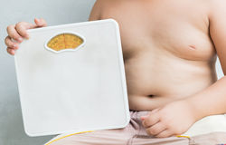 Obese fat boy holding Weight Scale. On gray background royalty free stock photos
