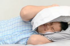 Obese fat boy lying in bed covering head with pillow. Because too loud annoying noise keeps his up all night long. Irritated child suffering from noisy Stock Photo