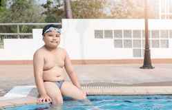 Obese fat boy sit on swimming pool Royalty Free Stock Photo
