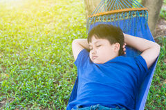 Obese fat boy sleep on cradle. In park stock photos