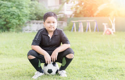 Obese fat boy soccer player sit on football Royalty Free Stock Photo