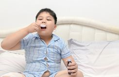 Obese fat boy take syrup on bed. Because of the flu and cough, Health care concept Stock Photo