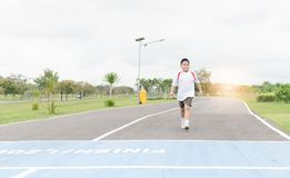 Free Obese Fat Boy Walking To The Finished Line. Stock Photo - 100321080