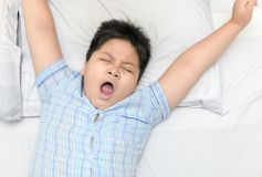 Obese fat boy yawn on bed in morning. Obese fat boy yawn on bed in morning, top view and healthy concept stock photos