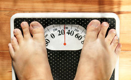 Obese feet on scale. Feet of a fat person on a weight scale (measuring both in pounds and kilograms) showing obesity Stock Photos