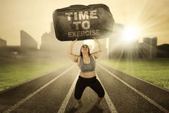 Obese female with boulder on track. Image of obese female lifting a big stone with text of time to exercise while running on the track Stock Images