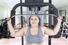 Obese female with cable machine in fitness center Stock Image