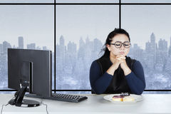 Obese female confused to eat donuts Royalty Free Stock Photography