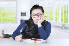 Obese female feels gorged with donuts. Image of obese female wearing glasses and holding a fork while bored with unhealthy food on a plate Royalty Free Stock Images
