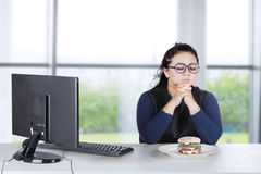 Obese female hesitates eat burger at home Stock Photography