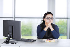 Obese female hesitates eat donuts at home Royalty Free Stock Photography