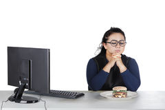 Obese female hesitates eat donuts on studio Stock Photos