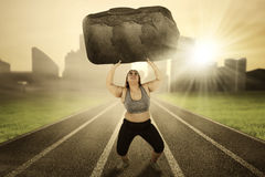 Obese female lifts stone on the track. Portrait of obese female lifting a big stone while running on the track Royalty Free Stock Photo