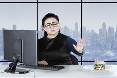 Obese female refuses burger in office Royalty Free Stock Photo