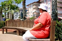Obese female tourist. Resting on a bench during a vacation stock photos