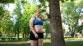 Obese girl exhausted after running workout, persistent efforts to lose weight royalty free stock photos