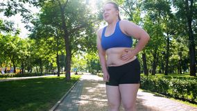 Obese girl jogging, suffocating, feels belly pain after tiresome workouts stock photos