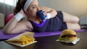 Obese lazy girl in sportswear drinking soda instead of training on yoga mat royalty free stock images