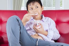 Obese little boy eating tasty ice cream at home royalty free stock image