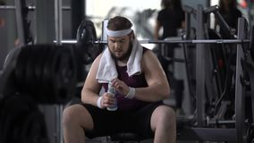 Obese male drinking water after barbell exercise, restoring aqua balance, diet. Stock footage stock video